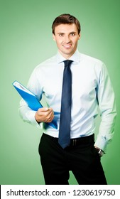 Portrait of happy smiling business man with blue folder, over green background