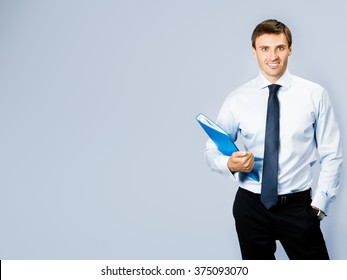 Portrait of happy smiling business man with blue folder, with copyspace, over grey background