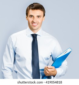 Portrait of happy smiling business man with blue folder, over grey background