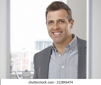 Portrait of happy smiling businessman at office. Suit with no tie, looking at camera.