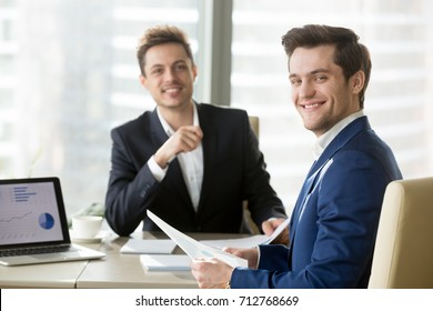 Portrait of happy smiling businessman sitting at meeting table with satisfied business partner, holding document with charts and looking in camera. Successful negotiation in office, good partnership