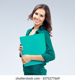 Portrait of happy smiling businesswoman in green confident clothing with folder, over grey background