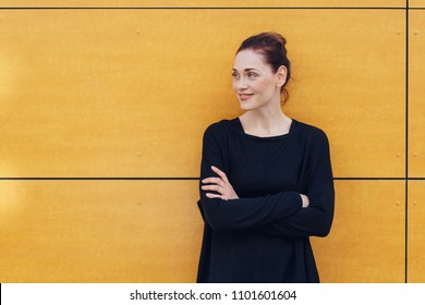 A portrait of a happy, smiling caucasian woman with folded arms leaning against yellow, urban wall.