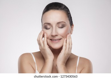 Portrait of happy smiling charming, beautiful woman touching skin or applying cream, with perfect skin after cream, balm, mask, lotion, isolated on grey background. Indoor, studio shot, copy space
