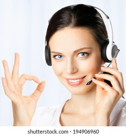 Portrait of happy smiling cheerful beautiful young support phone operator in headset showing okay gesture, at office