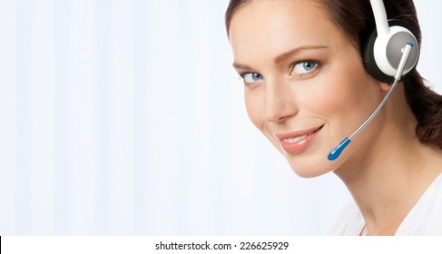 Portrait of happy smiling cheerful beautiful young support phone operator in headset, at office, with blank area for sign or copyspase