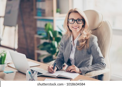 Portrait of happy smiling cheerful confident representative wearing formal outfit, she is sitting in front of computer and writing useful information
