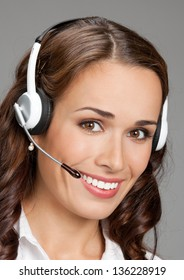 Portrait of happy smiling cheerful customer support phone operator in headset, over gray background