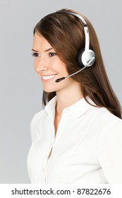 Portrait of happy smiling cheerful customer support phone operator in headset, over grey background
