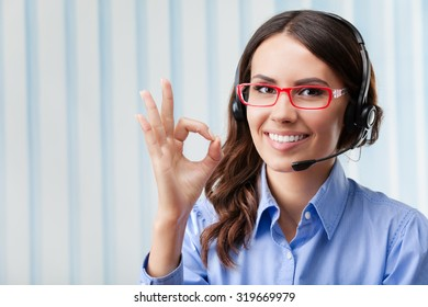 Portrait of happy smiling cheerful young support phone operator in headset, showing okay gesture, at office