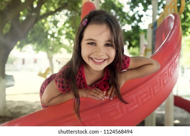 Portrait of Happy Smiling Child Girl Playing at Playground in Summer