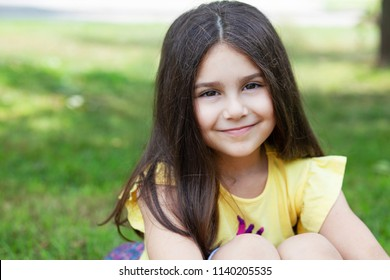 Portrait of a happy smiling child girl outdoor. Cute little girl playing in the park.