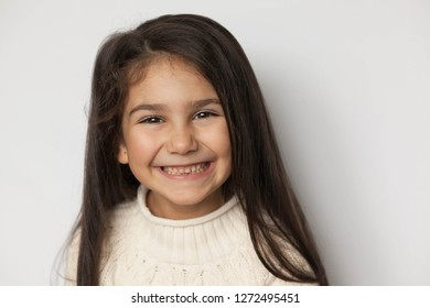 Portrait of a happy smiling child girl with long hear. Posivite laughing face. Toothless.