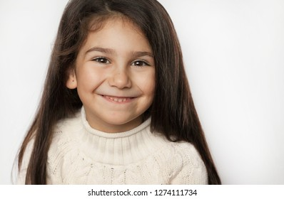 Portrait of a happy smiling child girl with long dark hear. Posivite laughing face. Toothless.