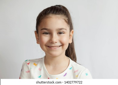 Portrait of happy smiling child girl on light background. Laughing people. Positive emotions.