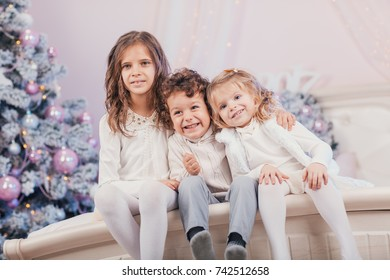 Portrait of happy smiling children near the Christmas tree. Xmas mood. Funny girls and a boy on the eve of a holiday.