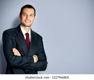 Portrait of happy smiling confident businessman in black suit and red tie, with crossed arms pose, empty copy space place for some text, advertising or slogan, standing against grey background