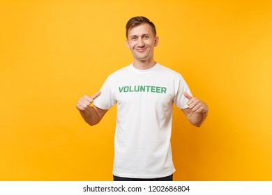 Portrait of happy smiling confident young man in white t-shirt with written inscription green title volunteer isolated on yellow background. Voluntary free assistance help, charity grace work concept