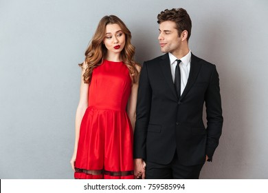 Portrait of a happy smiling couple dressed in formal wear standing while holding hands and looking at each other over gray wall background