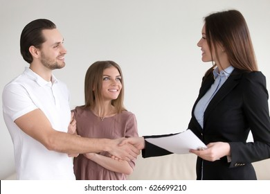Portrait of happy smiling couple and real estate broker shaking hands, young family meeting with banker to discuss mortgage loan, female advisor handshaking clients, visiting notary office