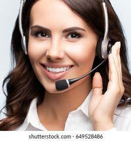 Portrait of happy smiling customer support female phone operator in headset, against grey background. Consulting and assistance service call center.