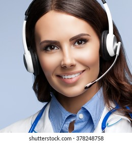 Portrait of happy smiling doctor in headset, on grey background