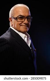 Portrait of happy smiling elderly man in elegant suit, looking at camera.