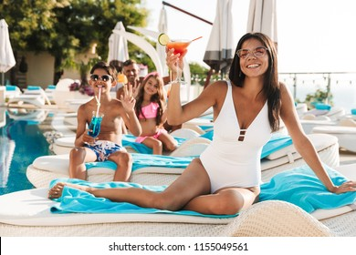 Portrait of happy smiling family with children lying on deckchairs near swimming pool outside hotel and drinking cocktails