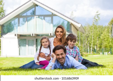 Portrait of happy smiling family and their children near their house