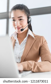 Portrait of happy smiling female customer support phone operator at workplace. Asian