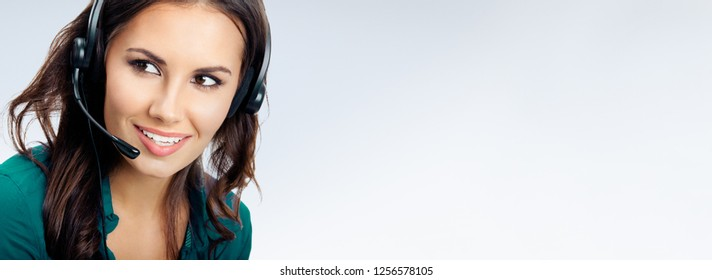 Portrait of happy smiling female phone operator in headset, green confident clothing, empty copyspace place for slogan or some advertising text message, over grey background. Call center concept.