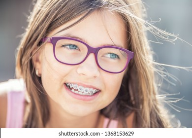 Portrait of happy smiling girl with dental braces and glasses.