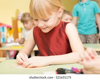 a portrait of a happy smiling girl draws bright colorful picture and sculpts from clay in kindergarten - Russia, Moscow - February 04, 2016