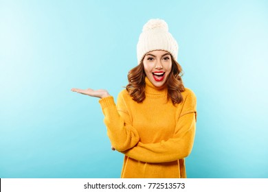Portrait of a happy smiling girl dressed in winter clothes presenting copy space on her palm isolated over blue background