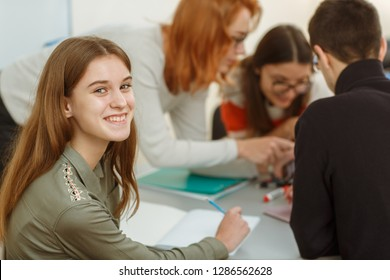 Portrait of happy smiling girl with long hair sitting near table. Students communicating and discussing interesting topic. Pupils during interactive lessons in private school of foreign languages.