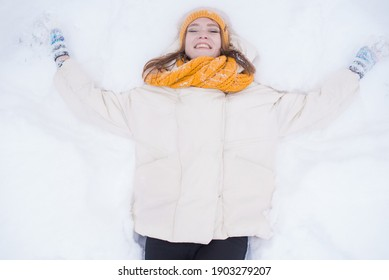 Portrait of a happy smiling girl lying on the snow on a snowy winter day