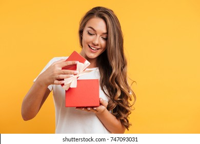 Portrait of a happy smiling girl opening a gift box isolated over yellow background - Shutterstock ID 747093031