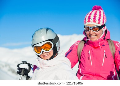 Portrait of happy smiling girl in ski goggles and with her mother, Zellertal, Austria. Focus on the girl