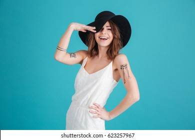 Portrait of a happy smiling girl wearing hat and posing isolated over blue