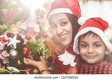 Portrait of happy smiling Indian/Asian Mother And Daughter in red Christmas hats near a Christmas tree