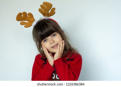 Portrait of happy smiling kid in a red knitted pullover with a Rudolf deer horn on head isolated on white background. Merry xmas. Moose horn. Carnaval costume.