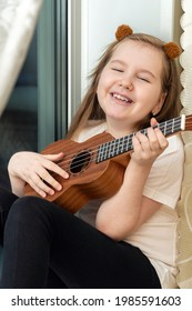 Portrait of happy smiling little girl in white t-shirt and black leggings sitting inside of home and playing ukulele. Hobbies and leisure activities concept. Vertical.