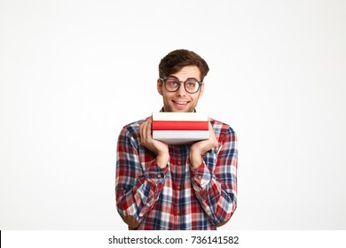 Portrait of a happy smiling male student in eyeglasses holding books at his face and looking up at copy space isolated over white background