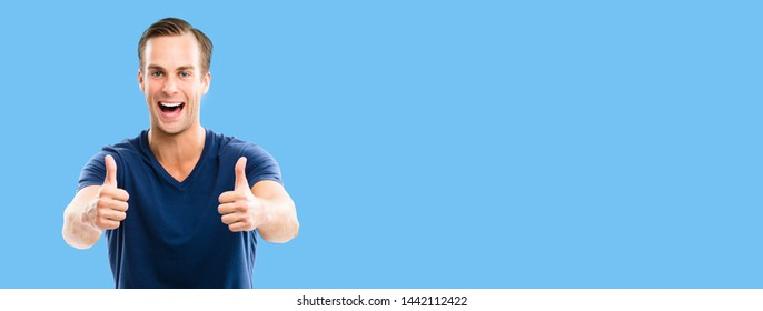 Portrait of happy smiling man in blue casual clothing, showing thumb up gesture, against blue color background. Male caucasian model at studio. Copyspace area for some ad sign text.