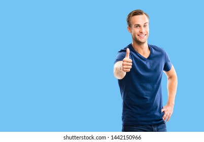 Portrait of happy smiling man in blue casual clothing, showing thumb up gesture, over blue color background. Male caucasian model at studio picture. Copy space area for some sign text.