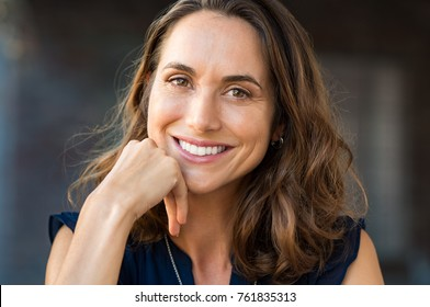 Portrait of a happy smiling mature woman with hand on chin looking at camera. Close up face of beautiful latin woman with brown hair outdoor. Cheerful hispanic woman closeup.
