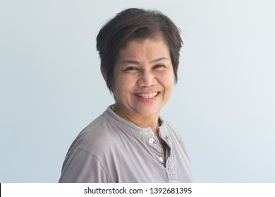 portrait of happy smiling middle aged old woman with wrinkle skin and slight grey hair