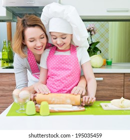 Portrait of happy smiling mother and daughter making pies together at the kitchen.