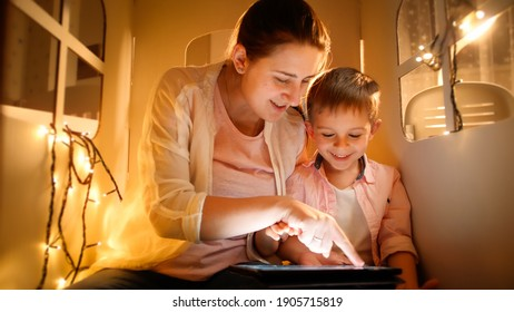 Portrait of happy smiling mother with little son playing and having fun with tablet computer in tent or small house at night. Concept of child education and family having time together at night.