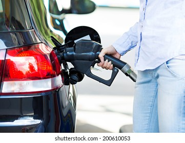 Portrait happy smiling pretty, attractive woman filling compact car tank with petrol at gas station isolated city background. Oil prices economy, energy cost, transportation industry, travel, concept